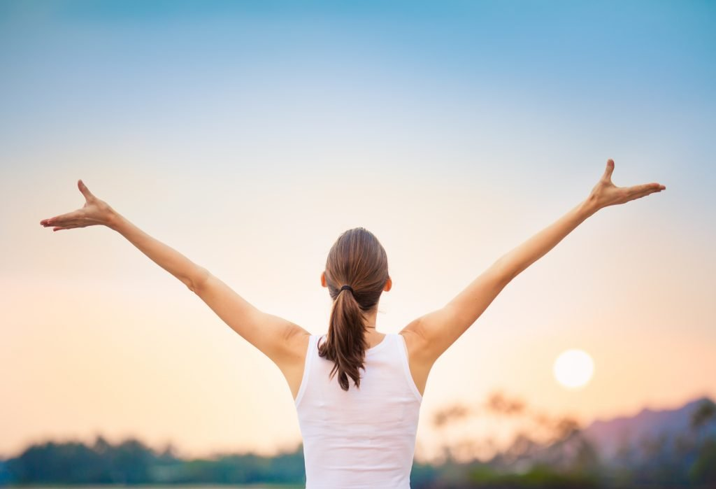 Woman facing away with arms raised in blissful balance.