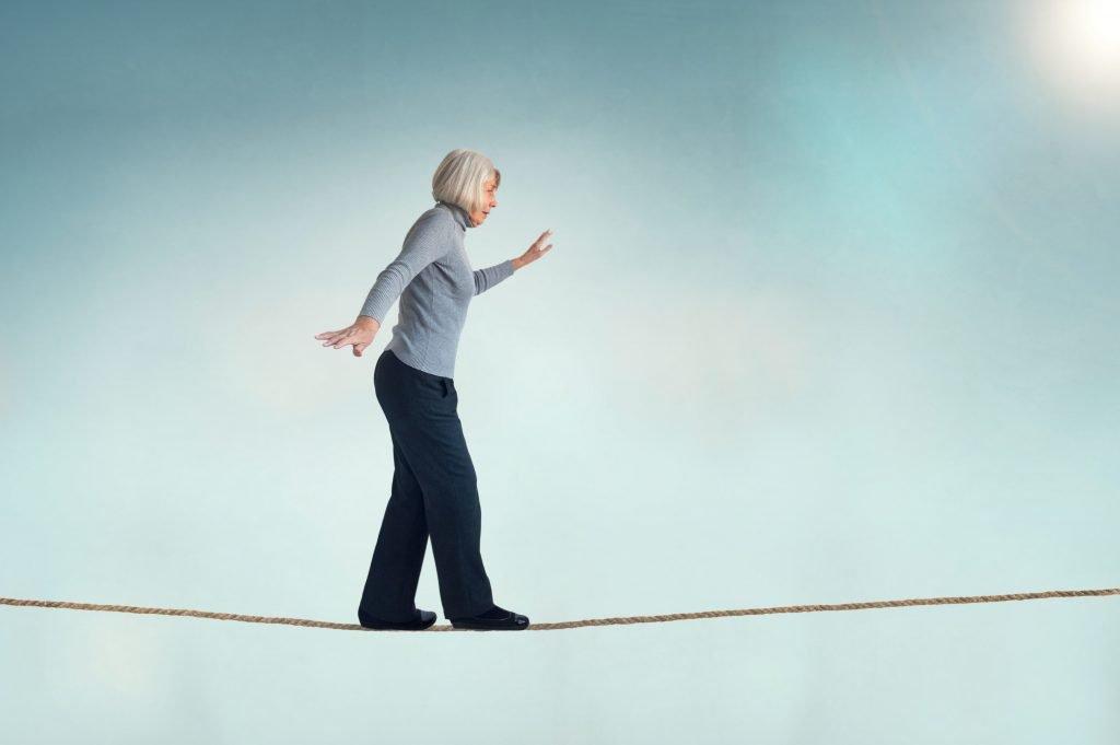 Older woman balancing walking tightrope.